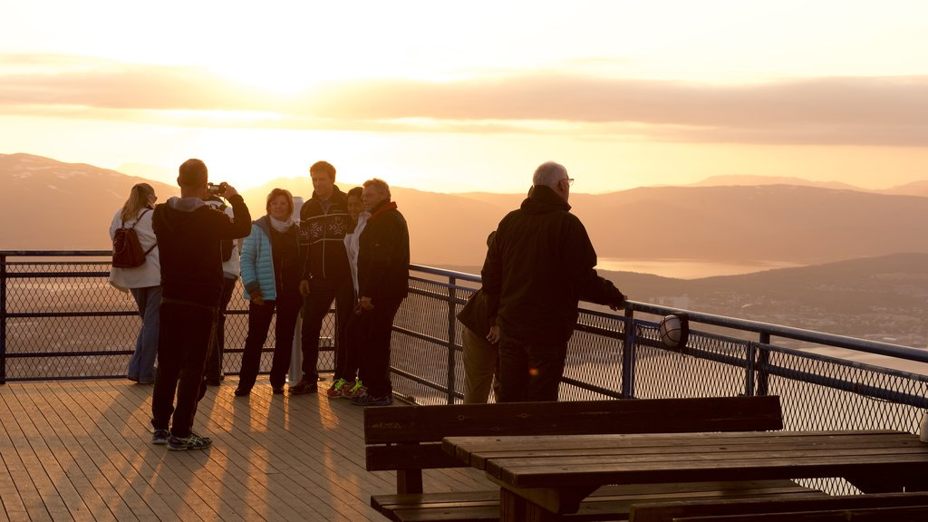 Tromso featuring views and a sunset as well as a small group of people