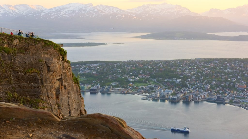 Tromso which includes a small town or village, a sunset and a lake or waterhole