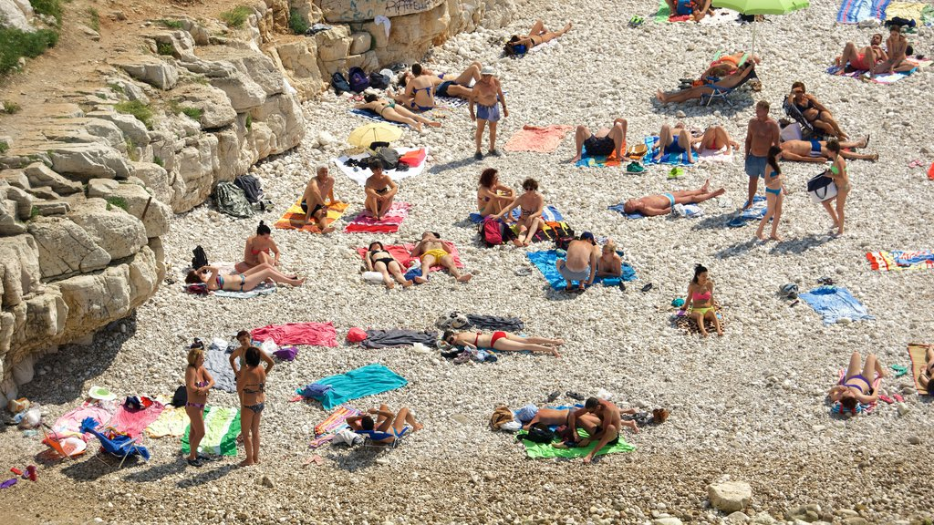 Polignano a Mare featuring a pebble beach as well as a large group of people