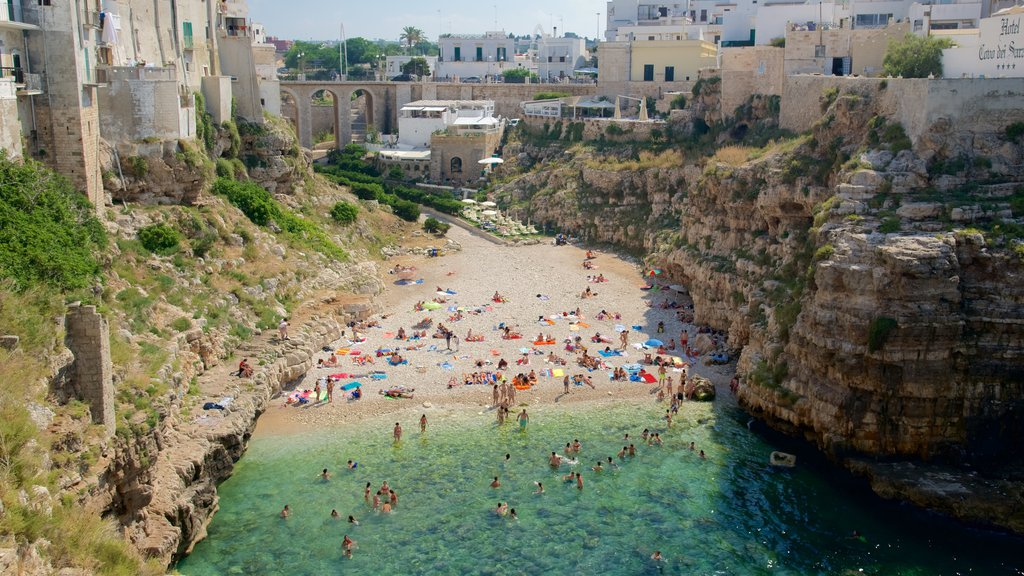 Polignano a Mare which includes a sandy beach and rocky coastline as well as a large group of people