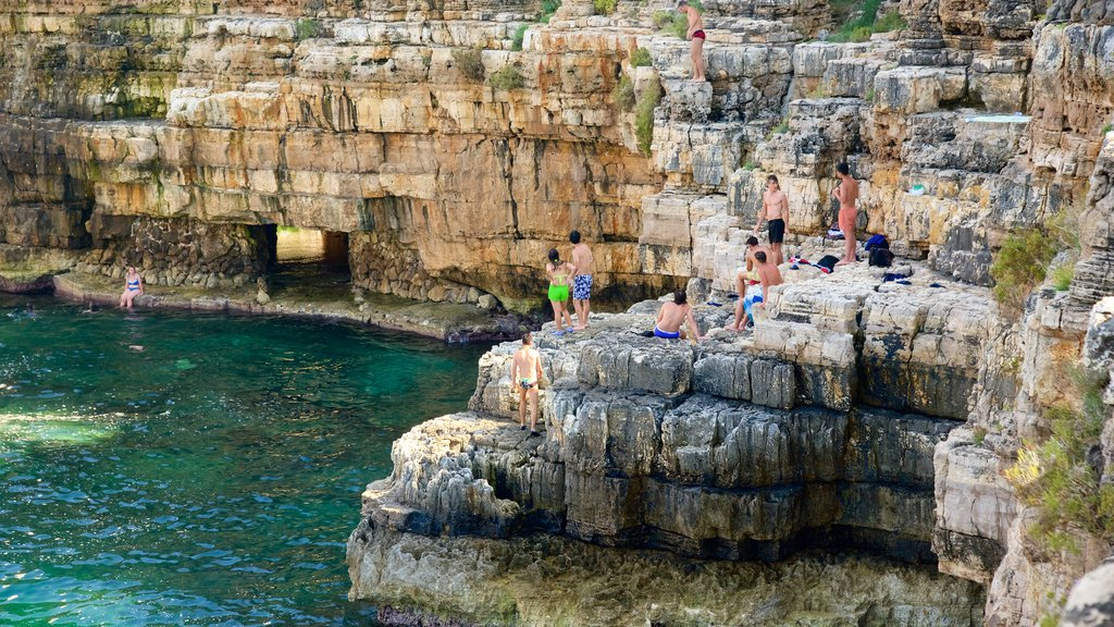 Polignano a Mare featuring rugged coastline as well as a large group of people