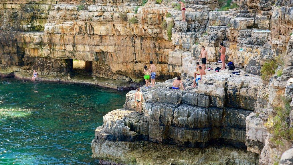 Polignano a Mare ofreciendo costa rocosa y también un gran grupo de personas