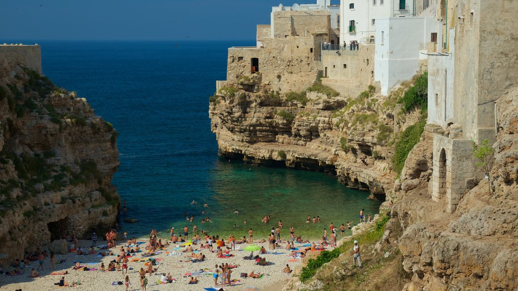 Polignano a Mare showing rugged coastline as well as a large group of people