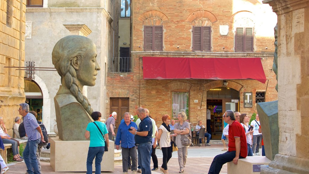 Pienza showing a statue or sculpture as well as a large group of people