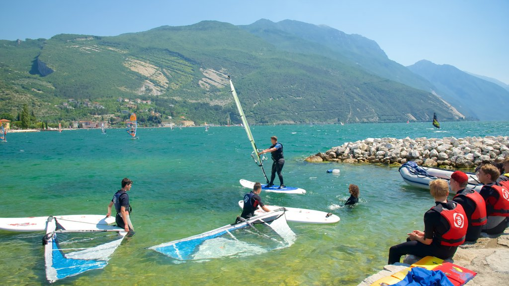 Nago-Torbole featuring rocky coastline and kite surfing as well as a small group of people