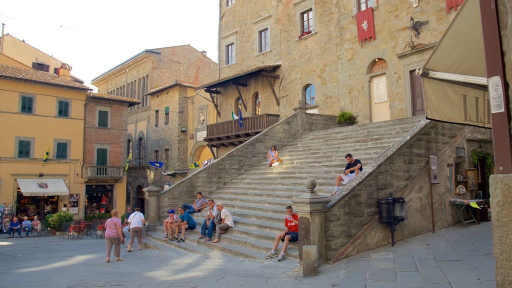 Cortona showing a sunset as well as a large group of people