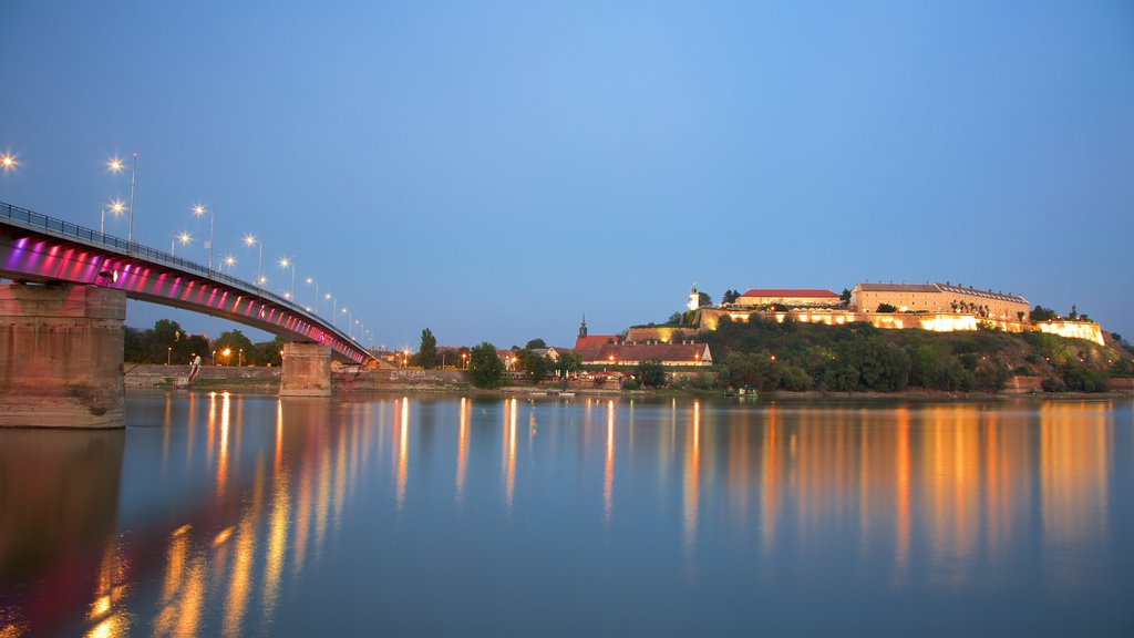 Petrovaradin Fortress showing a river or creek, night scenes and a bridge