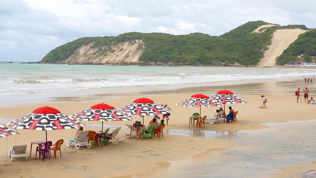 Praia de Ponta Negra caracterizando uma praia de areia e paisagens litorâneas assim como um pequeno grupo de pessoas