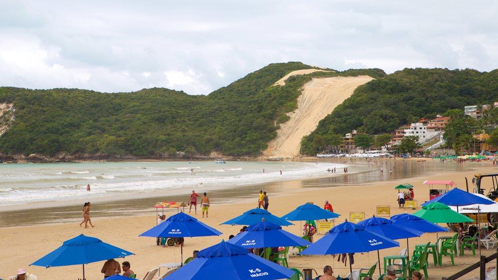 Praia de Ponta Negra mostrando uma praia de areia e paisagens litorâneas assim como um pequeno grupo de pessoas