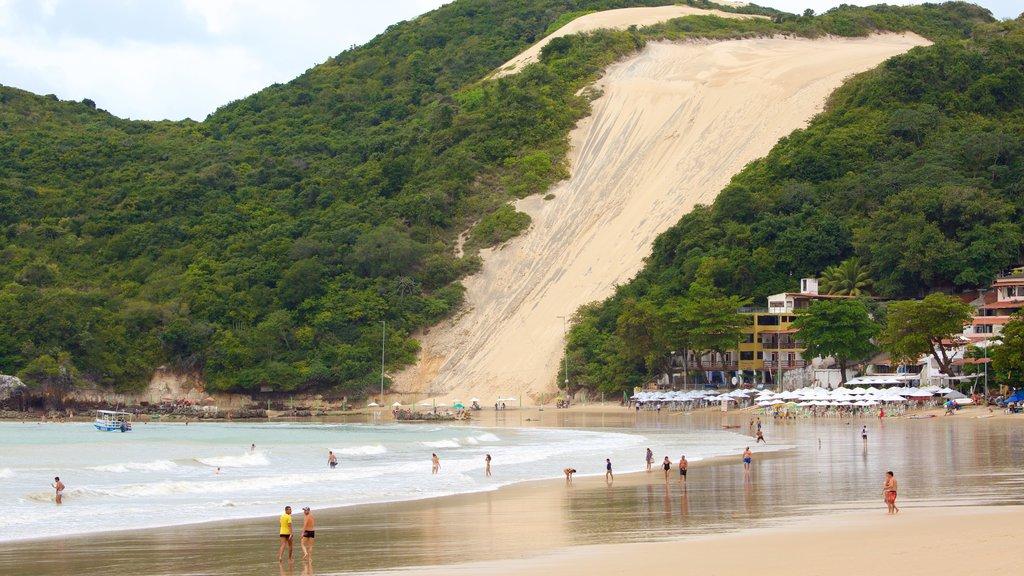 Praia de Ponta Negra caracterizando paisagens litorâneas e uma praia assim como um pequeno grupo de pessoas