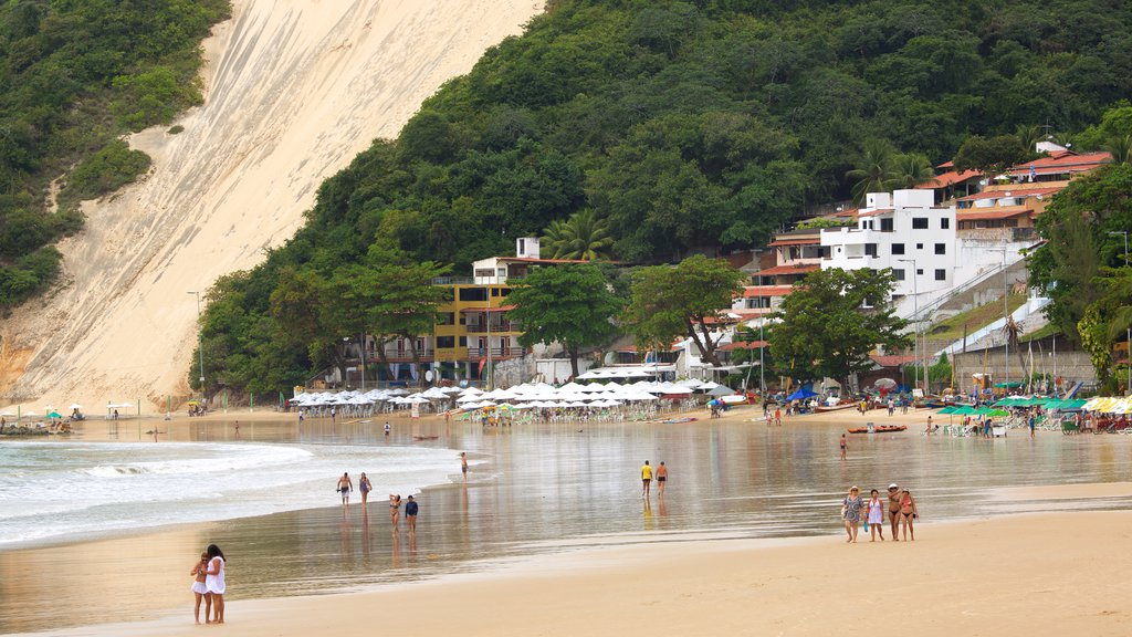 Praia de Ponta Negra mostrando paisagens litorâneas e uma praia de areia assim como um pequeno grupo de pessoas
