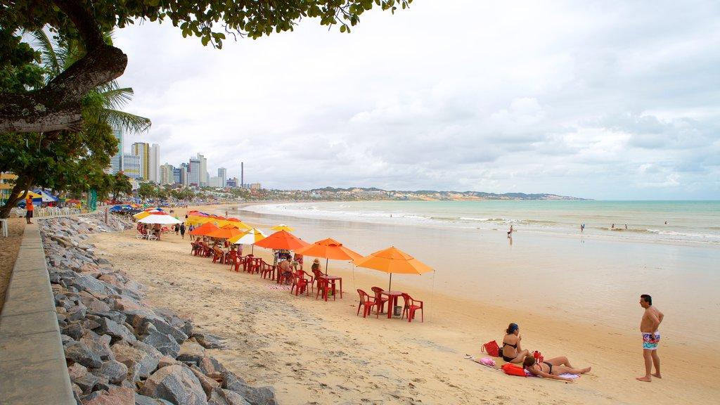 Praia de Ponta Negra que inclui paisagens litorâneas e uma praia assim como um pequeno grupo de pessoas