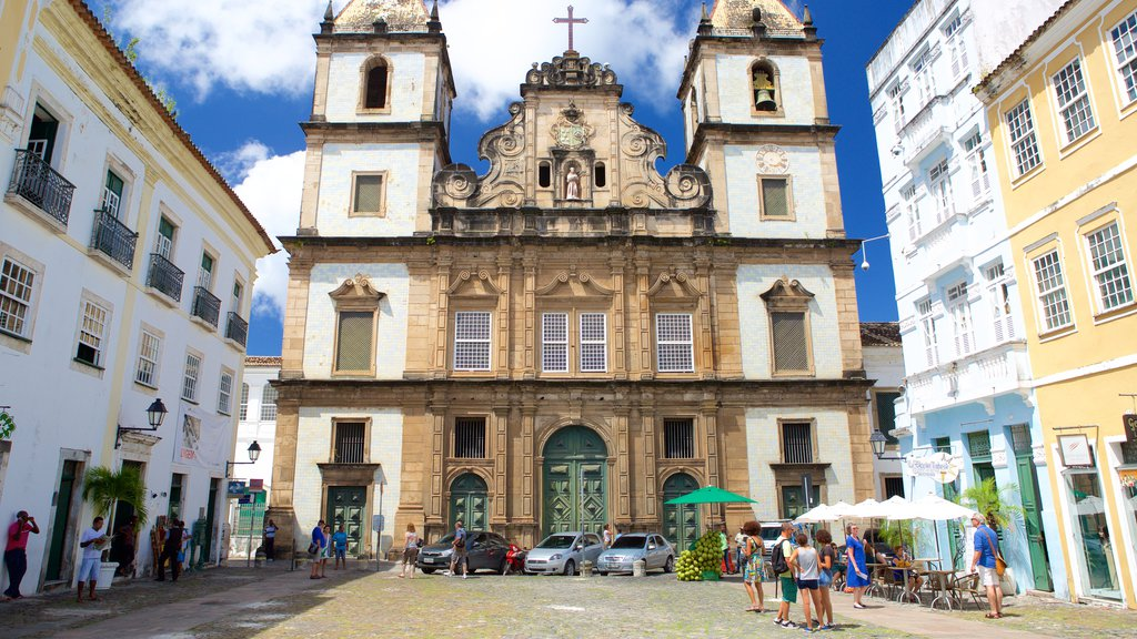 Pelourinho que inclui uma igreja ou catedral e cenas de rua assim como um pequeno grupo de pessoas