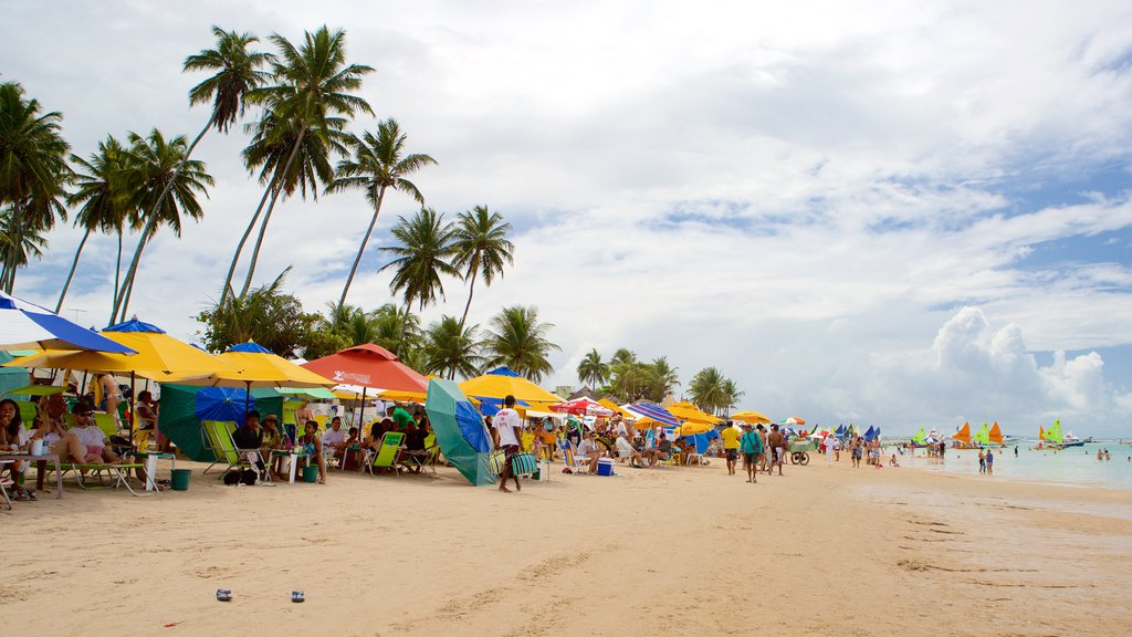 Porto de Galinhas which includes a sandy beach and general coastal views as well as a large group of people