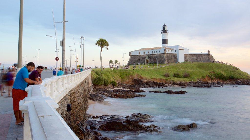 Praia do Farol da Barra caracterizando um farol e paisagens litorâneas assim como um pequeno grupo de pessoas