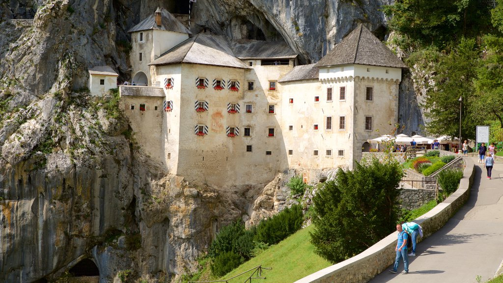 Predjama Castle featuring heritage architecture and a coastal town