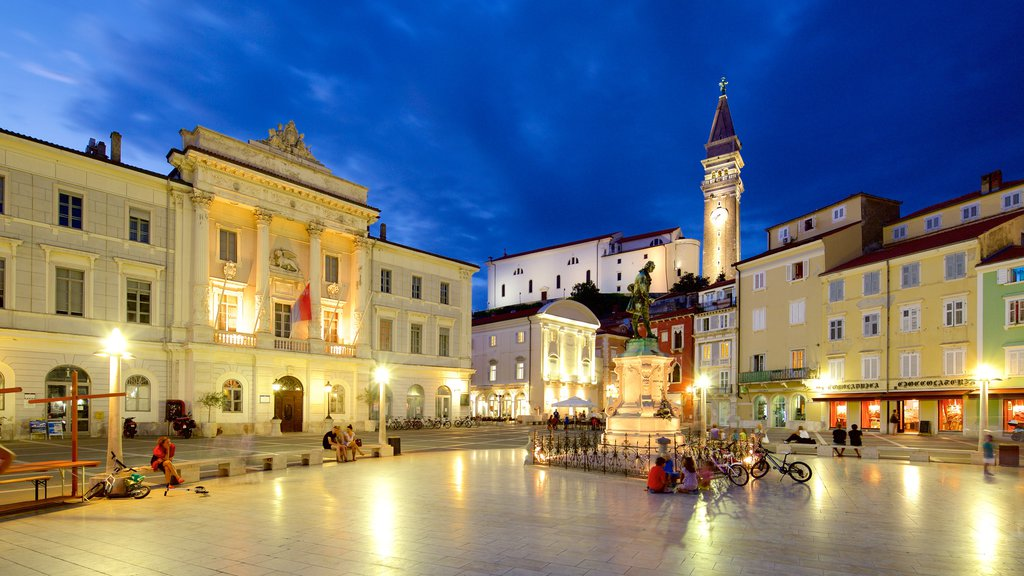 Piran featuring a square or plaza and night scenes as well as a large group of people