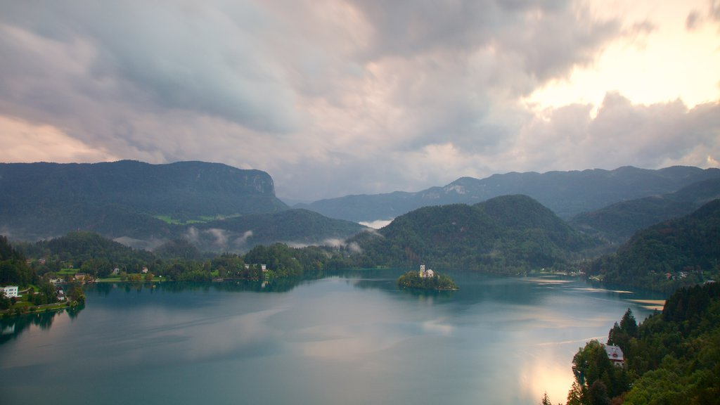 Lake Bled which includes mountains, a sunset and a lake or waterhole