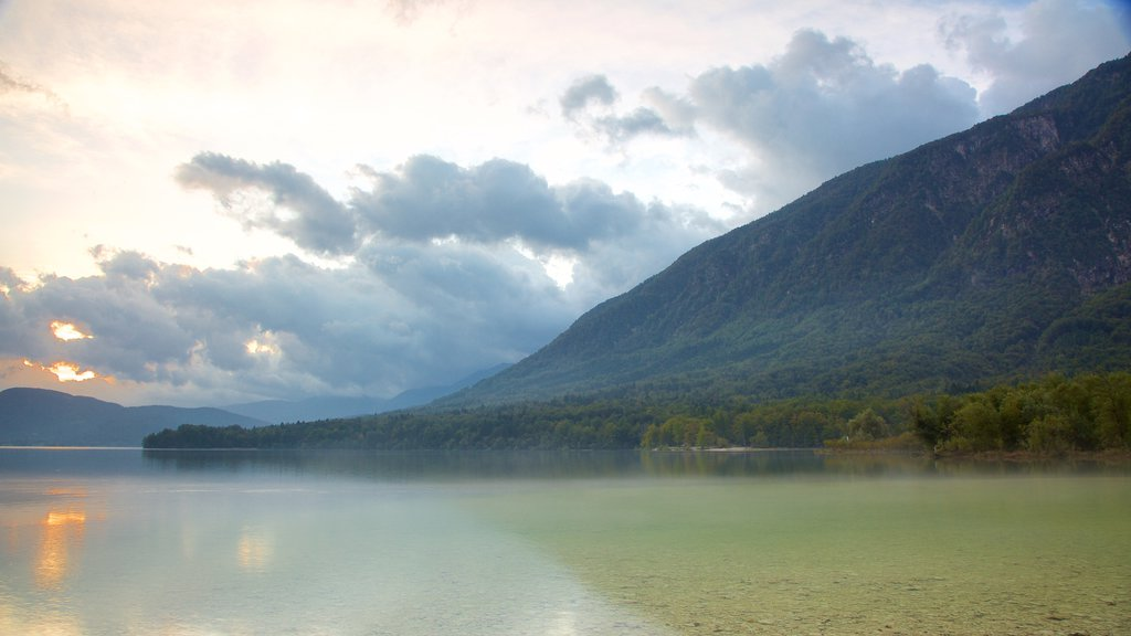 Lake Bohinj which includes mountains, a sunset and a lake or waterhole