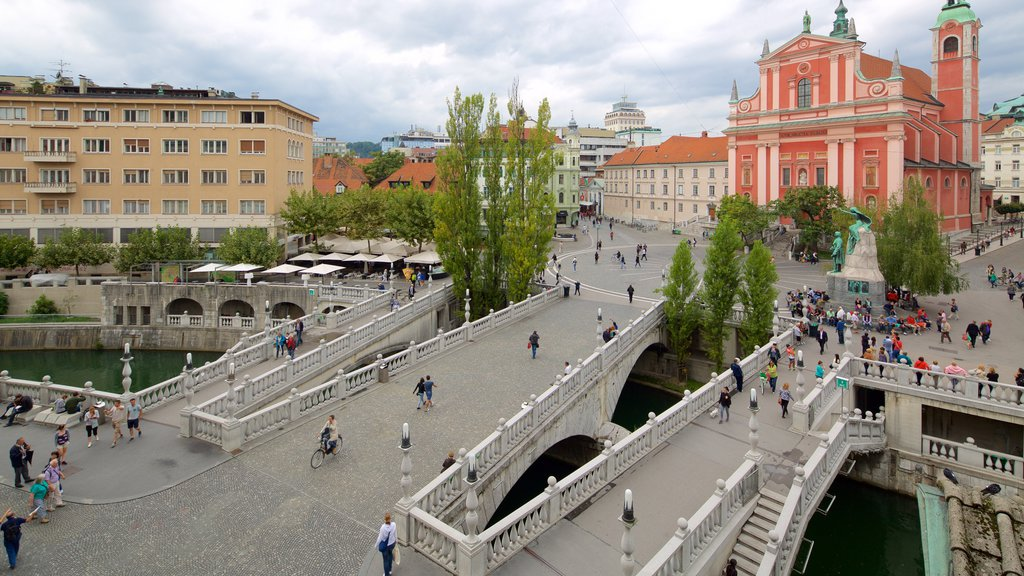 Triple Bridge showing a square or plaza and a city as well as a large group of people