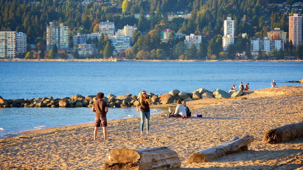 Stanley Park featuring a bay or harbor and a sandy beach as well as a small group of people