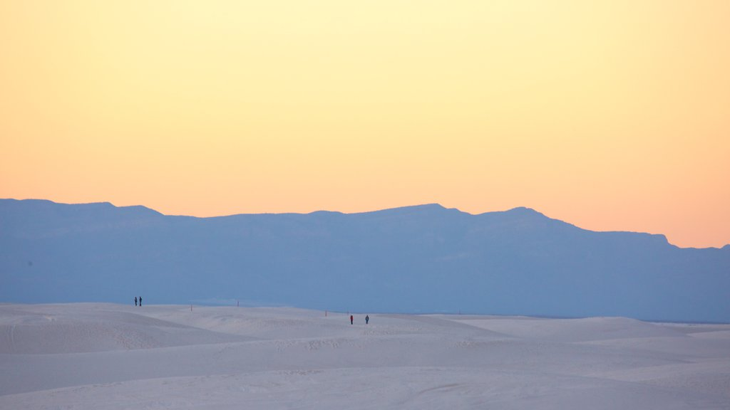 White Sands National Monument which includes a sunset, a sandy beach and mountains