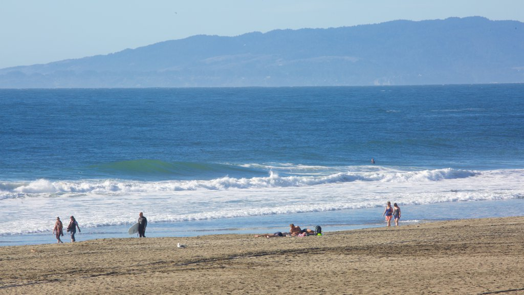 Ocean Beach showing a sandy beach and surfing as well as a small group of people