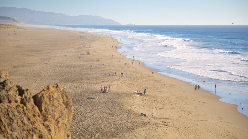 Ocean Beach which includes a beach and landscape views as well as a large group of people