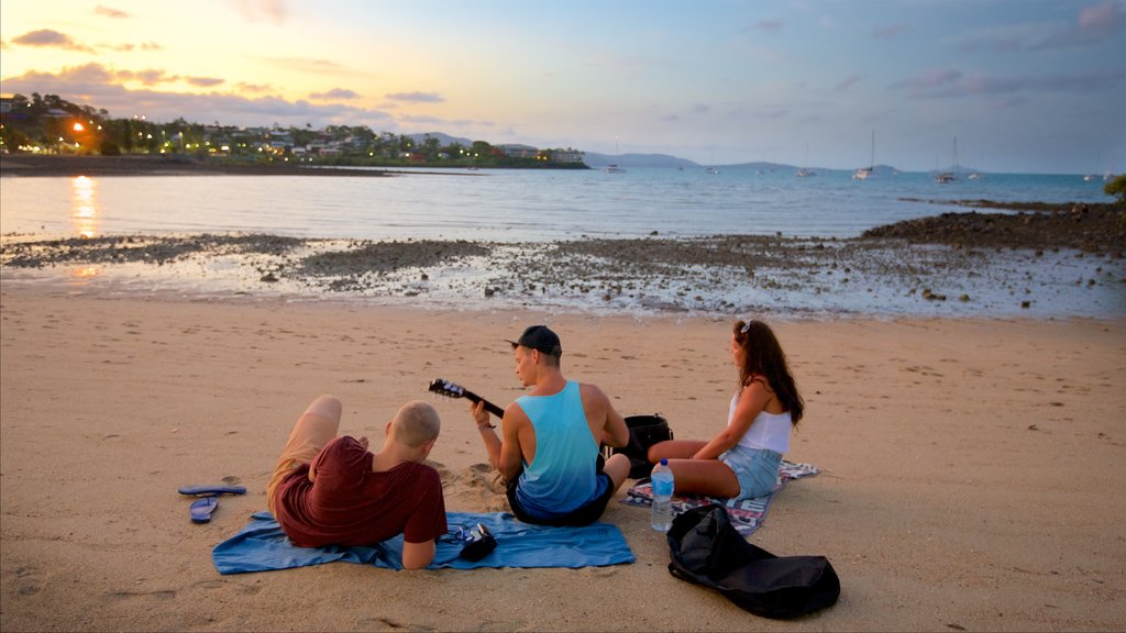 Airlie Beach showing a beach and a sunset as well as a small group of people