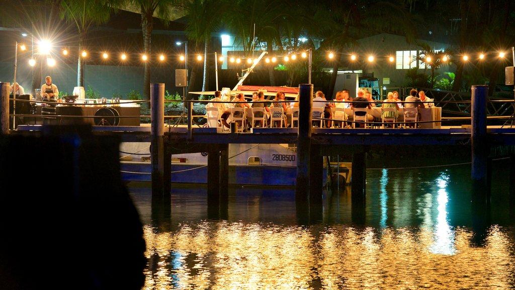 Hamilton Island Marina que incluye escenas nocturnas, comer al aire libre y salir a cenar