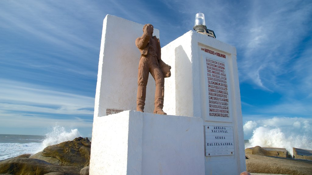 Punta del Diablo which includes a monument, general coastal views and signage