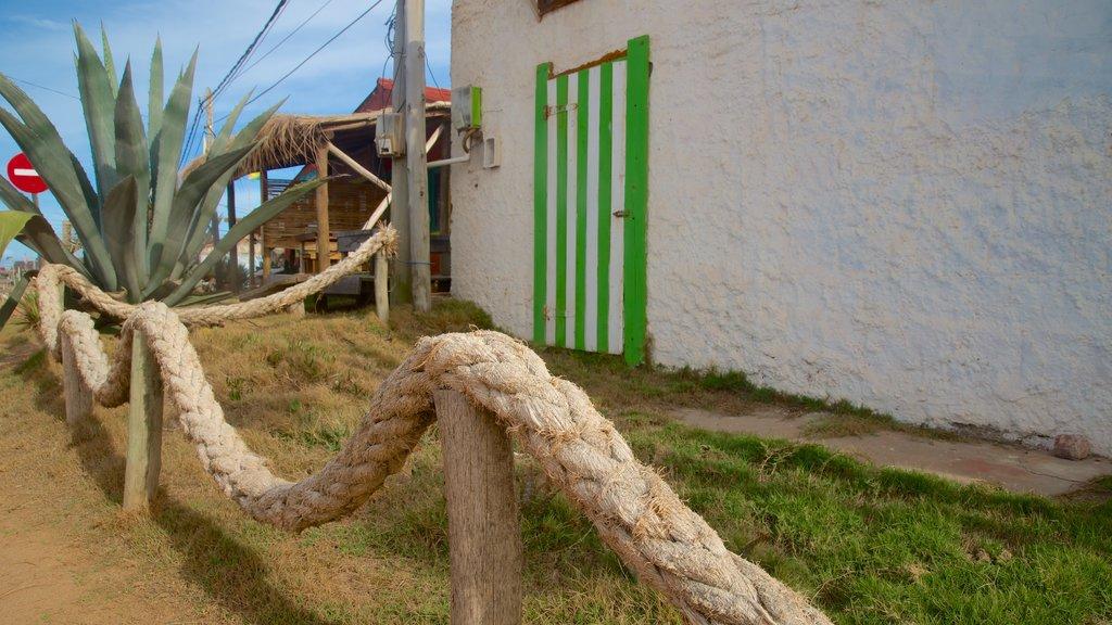 Punta del Diablo que incluye una pequeña ciudad o pueblo y una ciudad costera