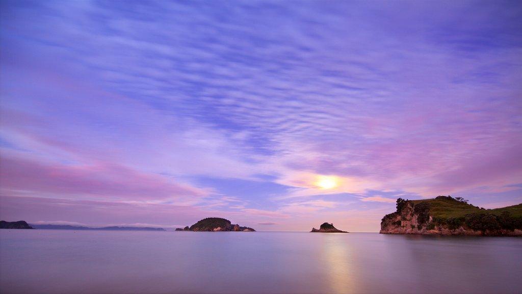 Hahei Beach que incluye una bahía o puerto, una puesta de sol y vistas de una isla