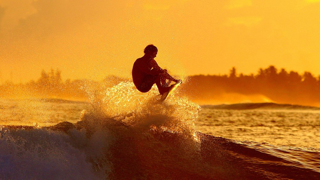 Maldives showing a sunset and surfing as well as an individual male