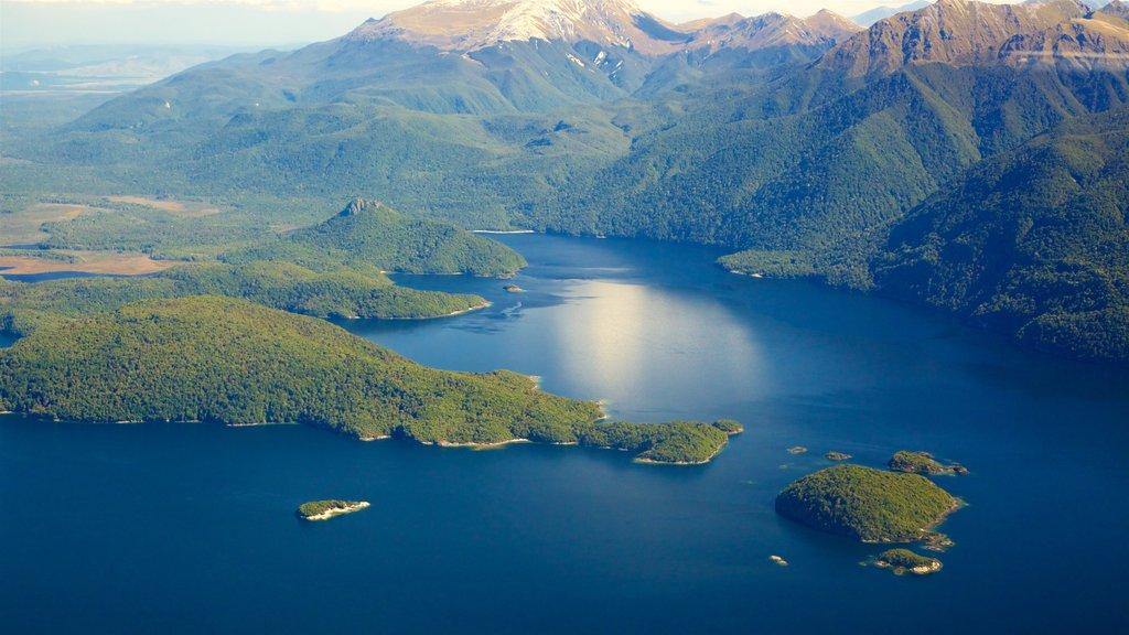 Lake Manapouri ofreciendo montañas, un lago o abrevadero y escenas forestales