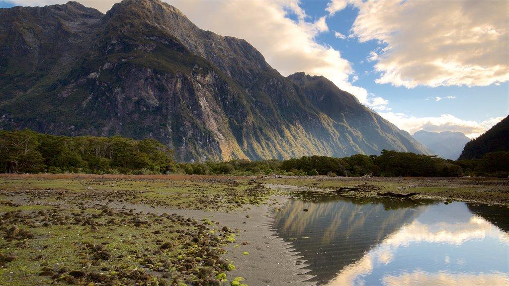 Parque nacional de Fiordland mostrando una puesta de sol, montañas y un lago o abrevadero