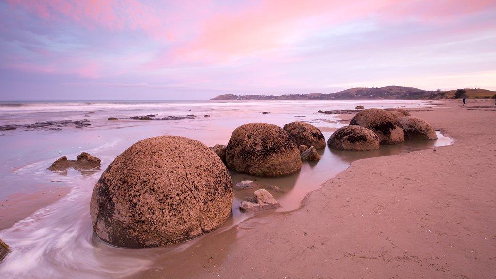 Moeraki Boulders mostrando una playa de arena, costa escarpada y una puesta de sol