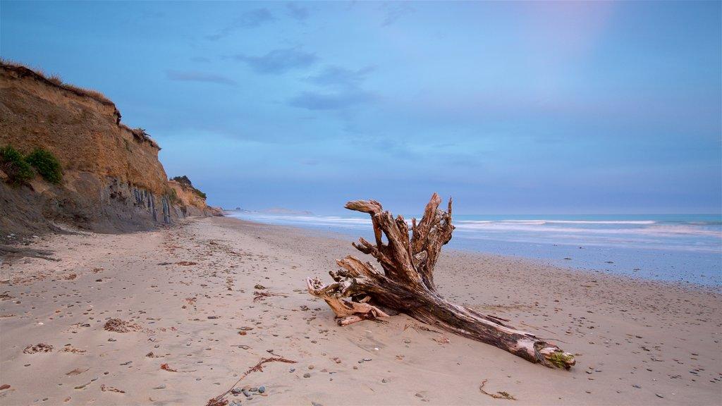 Oamaru ofreciendo una playa, una puesta de sol y costa escarpada