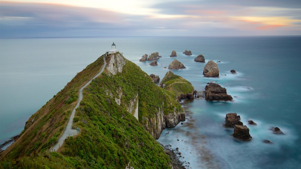 Nugget Point Lighthouse featuring mist or fog, rocky coastline and a bay or harbor