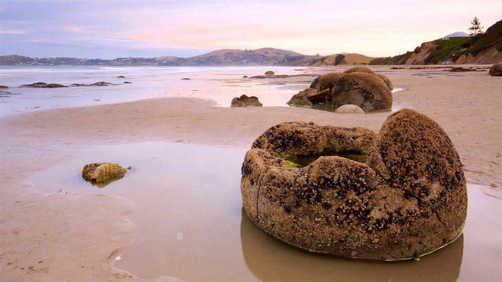 Moeraki Boulders que incluye una playa, una puesta de sol y costa rocosa