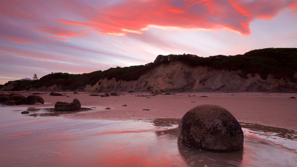 Moeraki Boulders que incluye una puesta de sol, una playa y costa escarpada