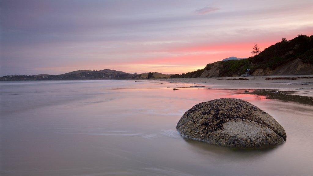 Moeraki Boulders ofreciendo una puesta de sol, vistas de paisajes y una playa