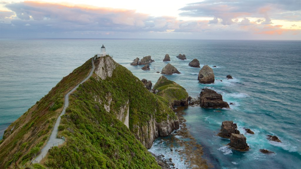 Nugget Point Lighthouse which includes rocky coastline, a sunset and a lighthouse