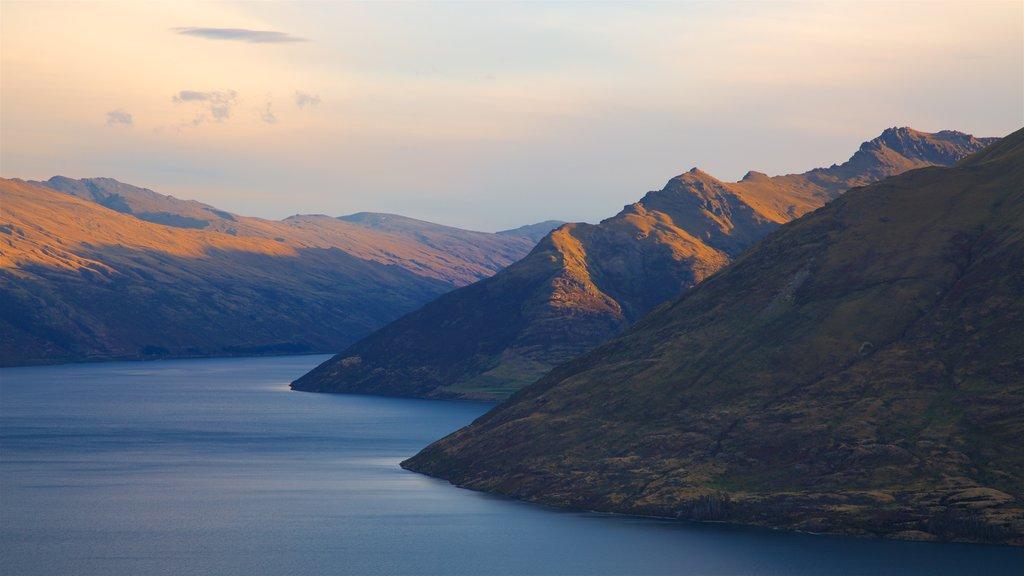 Pico Cecil que incluye un lago o abrevadero, montañas y una puesta de sol