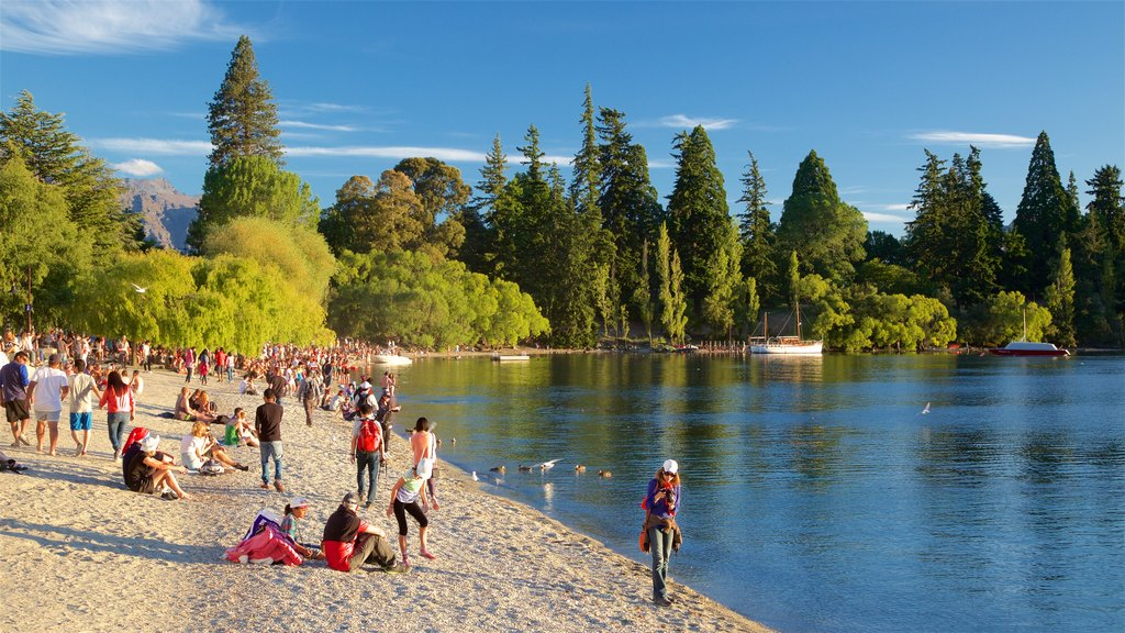 Queenstown Beach showing a pebble beach and a lake or waterhole as well as a large group of people