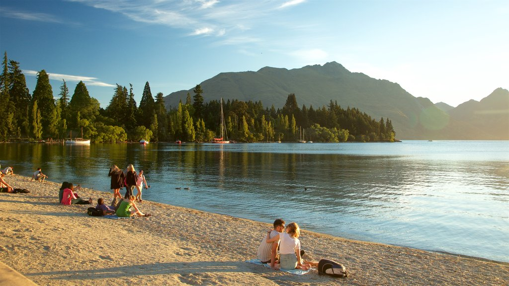 Queenstown Beach featuring mountains, a sunset and a lake or waterhole