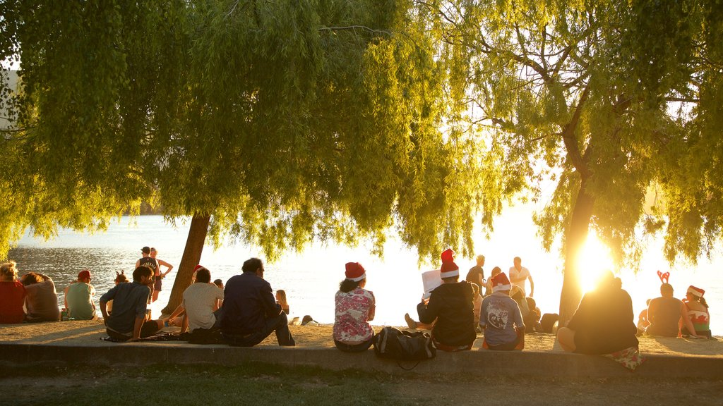 Centro de Queenstown que incluye una puesta de sol y un lago o abrevadero y también un gran grupo de personas