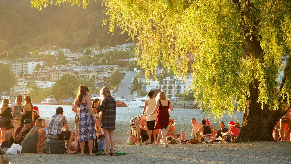 Playa de Queenstown que incluye una pequeña ciudad o pueblo, un lago o abrevadero y una puesta de sol
