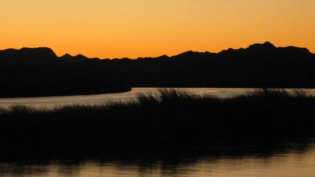 Yuma which includes a sunset, a river or creek and mountains