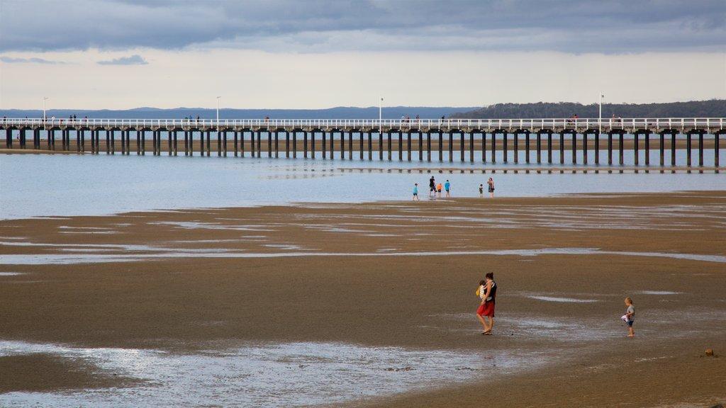 Urangan ofreciendo una playa de arena y vistas generales de la costa y también una familia